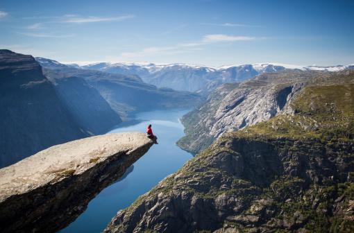 Człowiek Siedzi Na Trolltunga W Norwegii - zdjęcia stockowe i więcej obrazów Aranżować