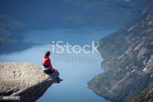 man sitting on trolltunga rock above lake in norway