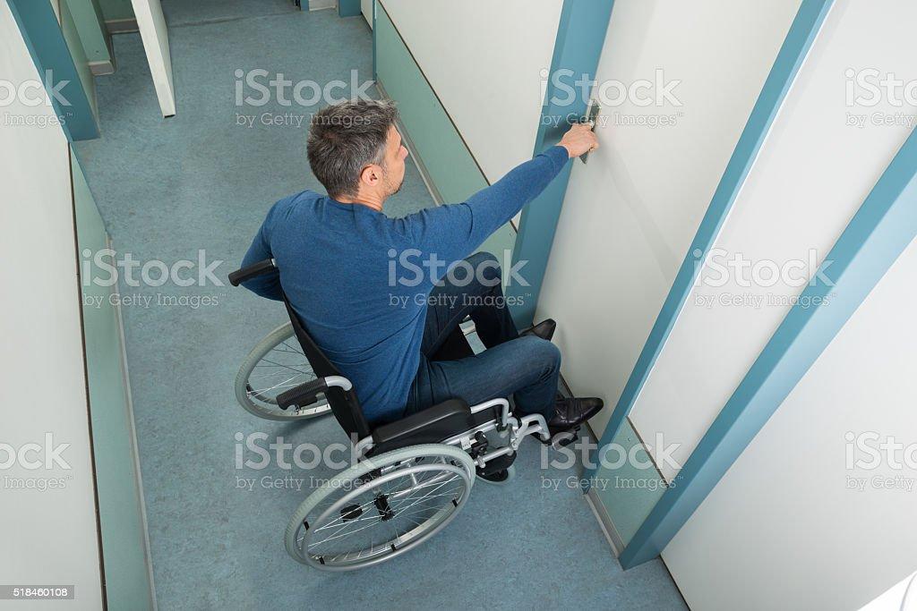 Man Sitting On Wheelchair Opening Door stock photo