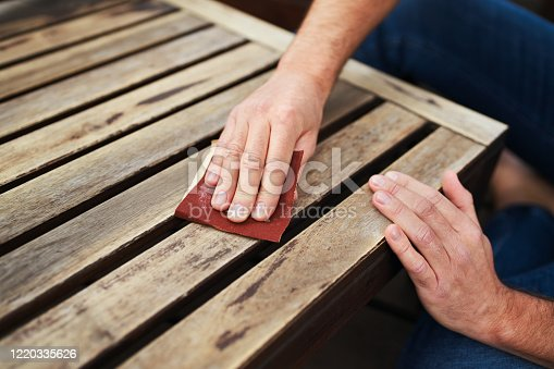Man sitting outdoors on terrace and sanding wooden furniture