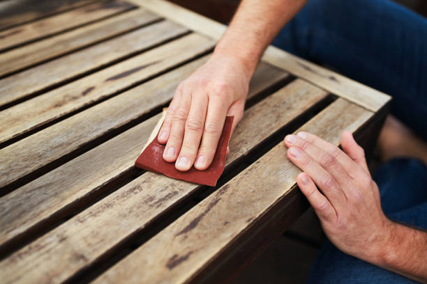 Man sitting outdoors on terrace and sanding wooden furniture stock photo