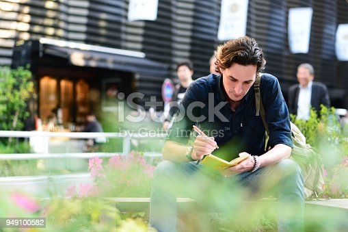 A mid adult man sitting outside in the late afternoon, writing something on a notebook.