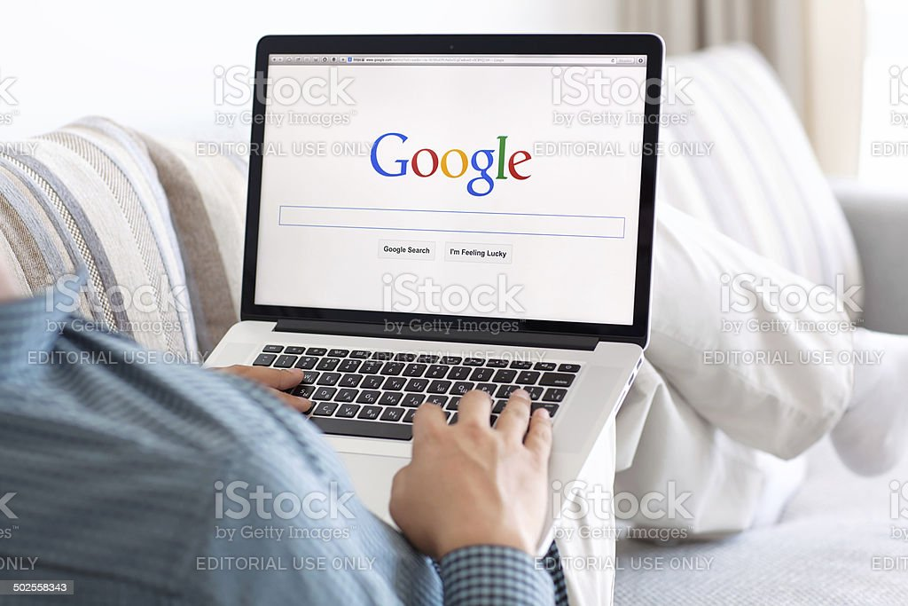 man sitting the MacBook retina with site Google on screen royalty-free stock photo