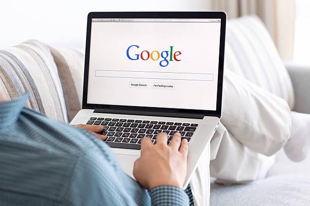 mann, sitzend auf der netzhaut macbook mit website google auf dem bildschirm - sucht stock-fotos und bilder