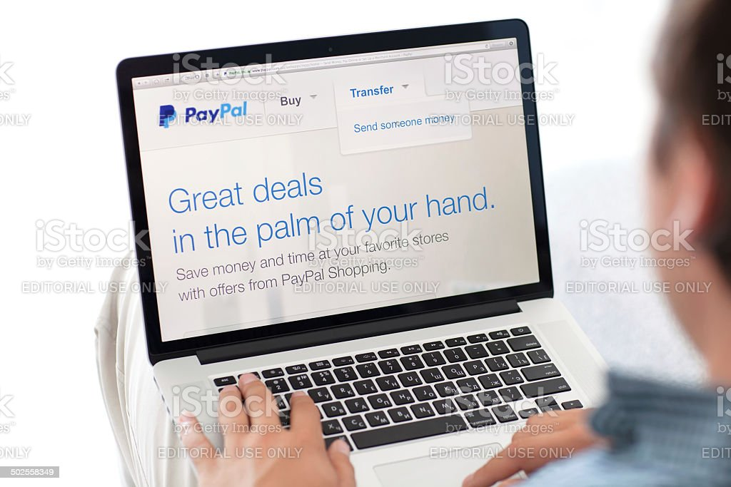 man sitting the MacBook retina with site PayPal on screen stock photo
