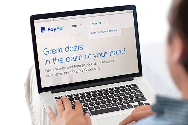 uomo seduto a retina macbook il sito paypal su schermo - paypal foto e immagini stock