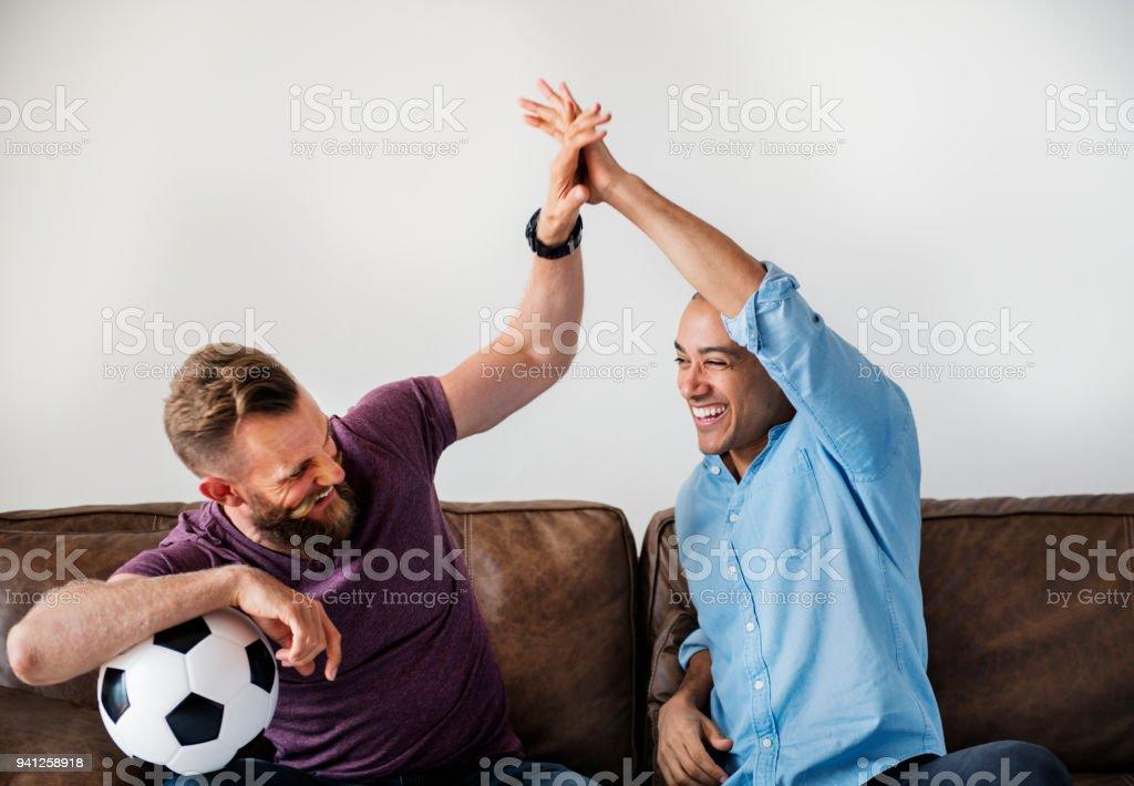 Hombre sentados juntos en un sofá viendo deporte - foto de stock