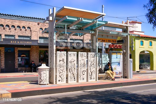 Man sitting waiting at the streetcar stop on 4th Ave in Tucson