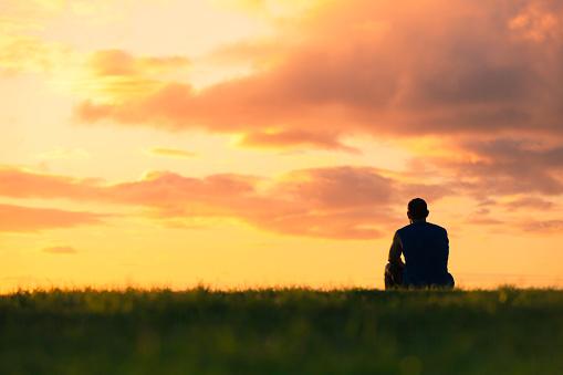 Man Sitting Watching Sunset - zdjęcia stockowe i więcej obrazów Aspiracje