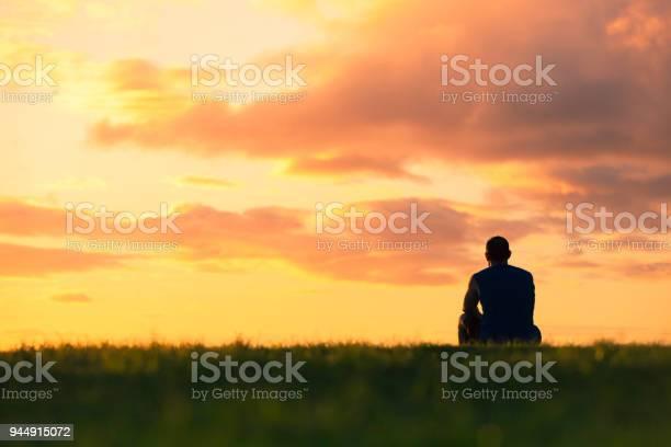 Photo of Man sitting watching sunset