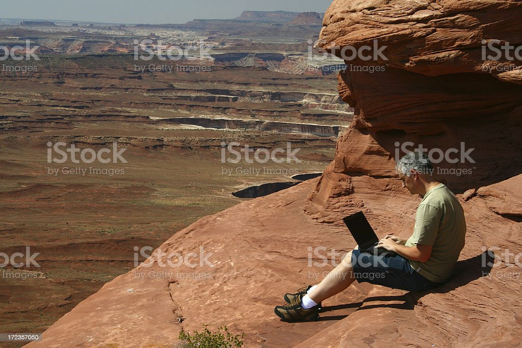 Man sitting with a laptop in canyonlands royalty-free stock photo