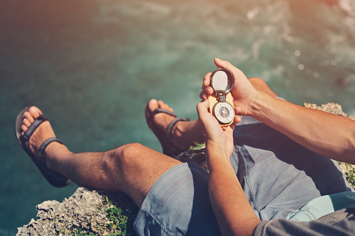 Man sitting with compass above the ocean