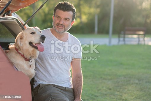 517930062istockphoto Man sitting with his dog on the car trunk 1163730860