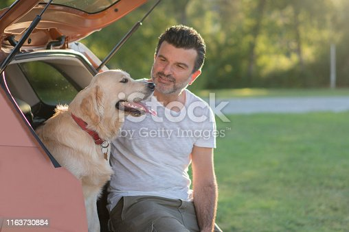 517930062istockphoto Man sitting with his dog on the car trunk 1163730884