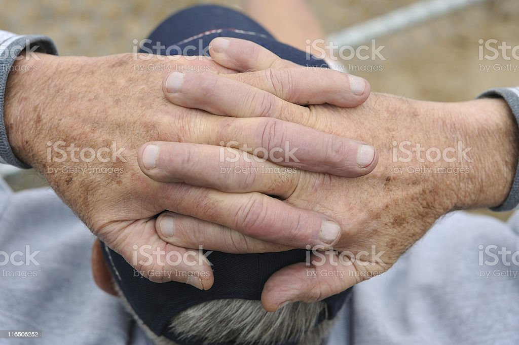 Man sitting with his hands clasped together on his head stock photo