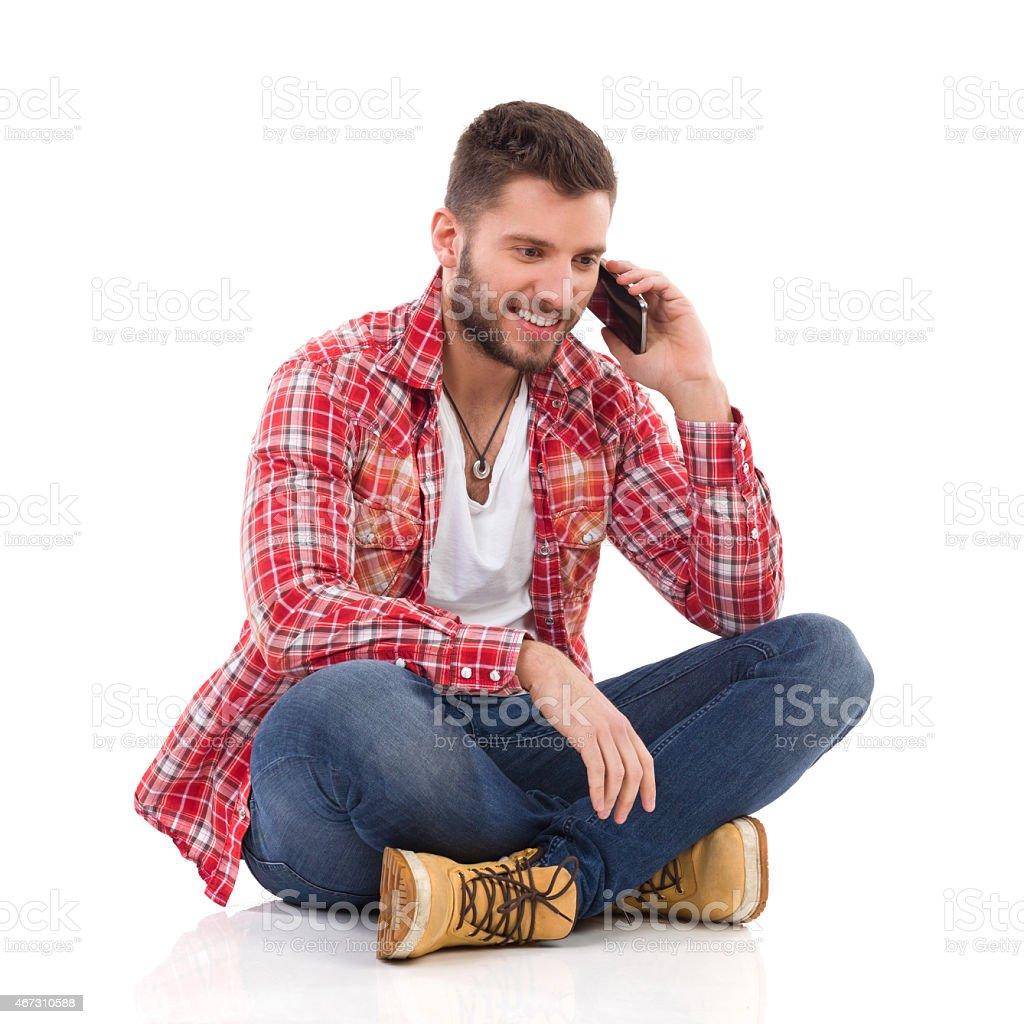 Homme assis avec les jambes croisées et parlant au téléphone - Photo