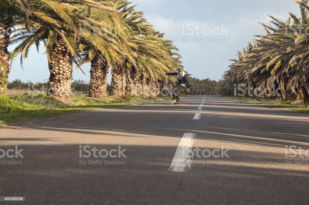 Man skateboarding on open road with palm trees stock photo