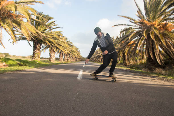 man skateboarding on open road with palm trees - skate liberdade gorro imagens e fotografias de stock