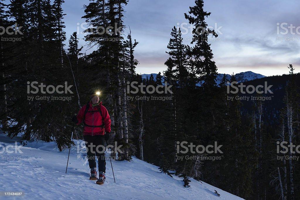 Man Ski Touring at dusk with Headlamp stock photo