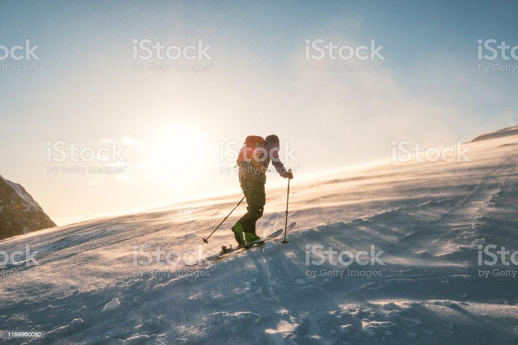 Man Skifahrer mit Rucksack Trekking auf Schneeberg mit Sonnenlicht - Lizenzfrei Abenteuer Stock-Foto