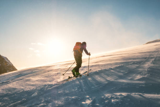 Man skier with backpack trekking on snow mountain with sunlight stock photo