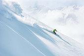 Male skier skiing down a steep ski slope on fresh powder snow
