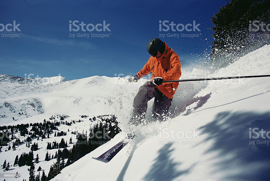 Man skiing down mountainside stock photo