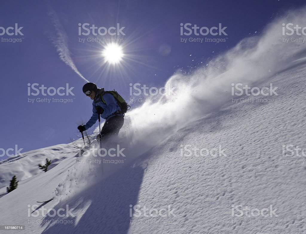 Man skiing down slope with blue sky and sun background stock photo