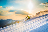 Man skiing and speeding down on ski slope at dusk, snowcapped mountain in background.