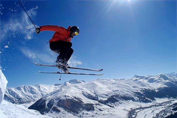 Man skiing in the mountains doing a jump trick stock photo