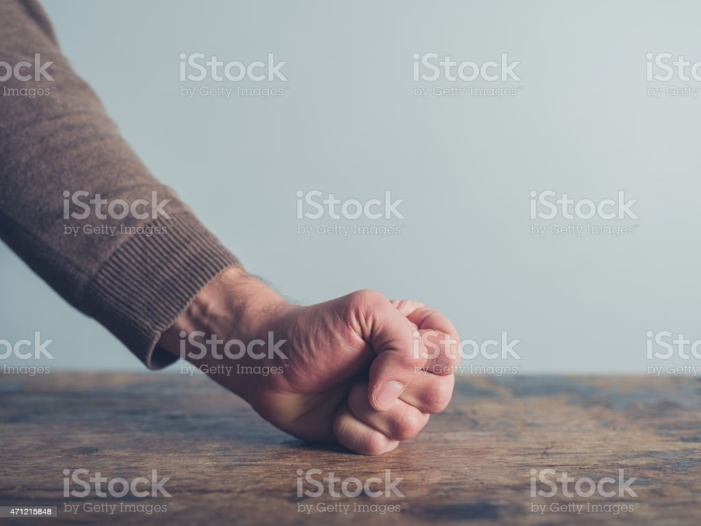 Man slamming his fist on table stock photo