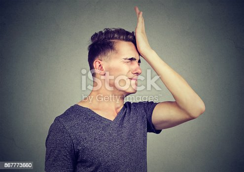 istock Man slapping hand on head having regrets isolated on gray background. Negative human emotion feeling 867773660