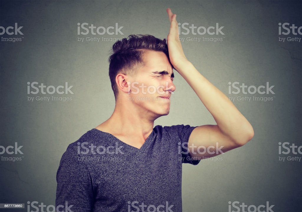 Man slapping hand on head having regrets isolated on gray background. Negative human emotion feeling stock photo