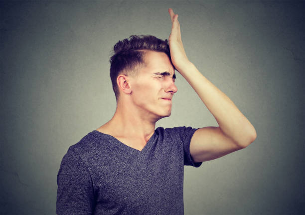 man slapping hand on head having regrets isolated on gray background. negative human emotion feeling - reminder stock photos and pictures