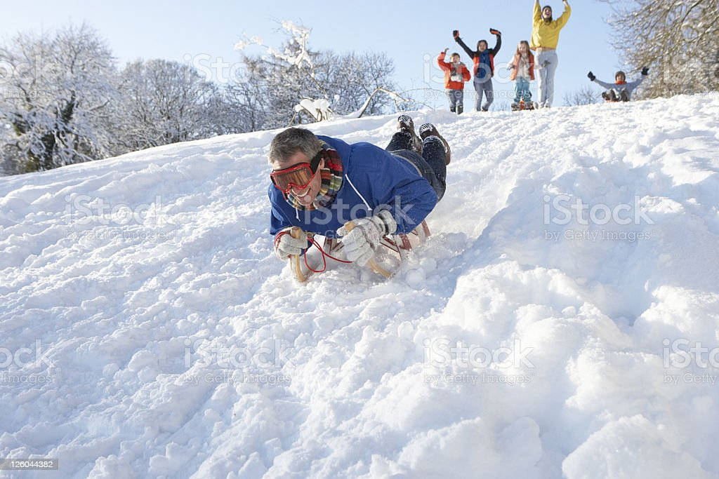 Man Sledging Down Hill With Family Watching stock photo