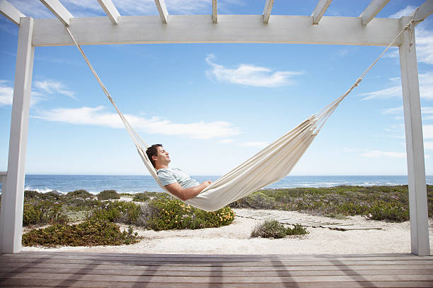 man sleeping in a hammock - hangmat stockfoto's en -beelden
