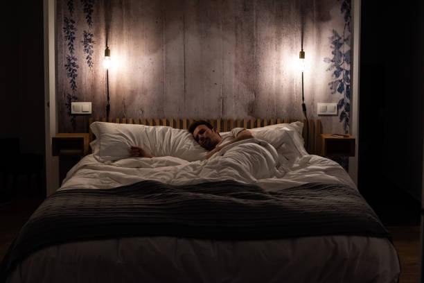 Man sleeping in bed in a modern beautiful bedroom stock photo