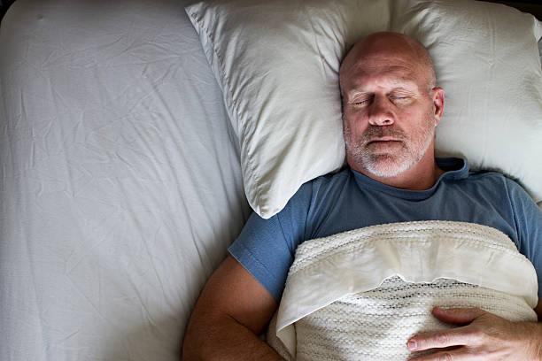 homme dormant dans un lit - technique photographique photos et images de collection
