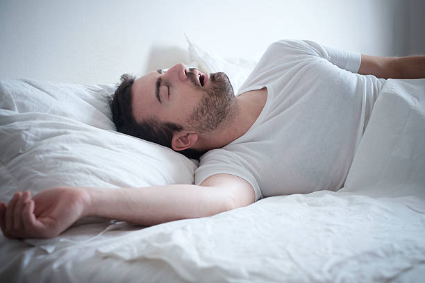 Man sleeping in his bed and snoring loudly - foto de acervo