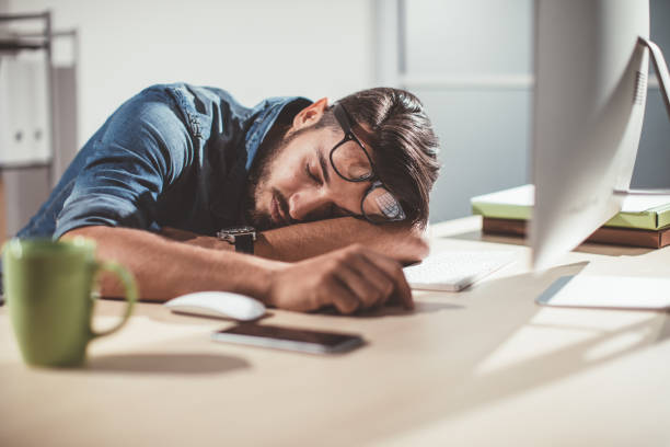 man sleeping in office - sleeping in work stock photos and pictures