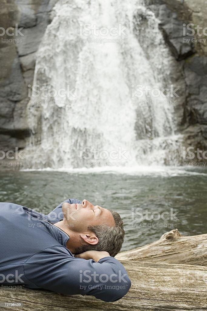 Man sleeping near a waterfall stock photo