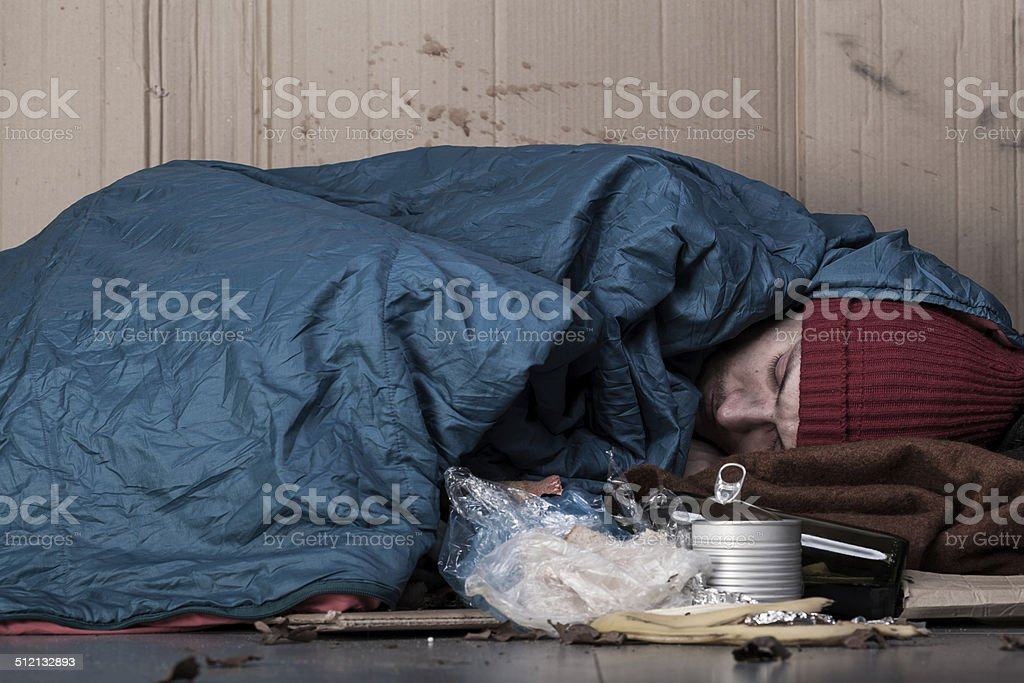 Man sleeping next to the trash stock photo