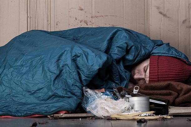 hombre durmiendo junto al poner verde - sin techo fotografías e imágenes de stock