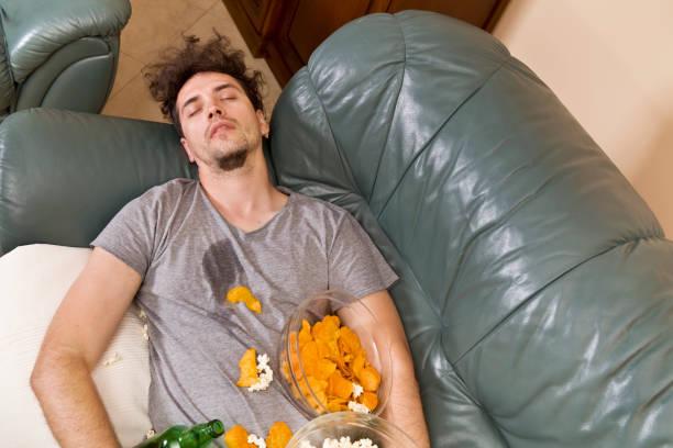 Ein Mann auf einer Couch in einem Gewirr von Junk-food – Foto