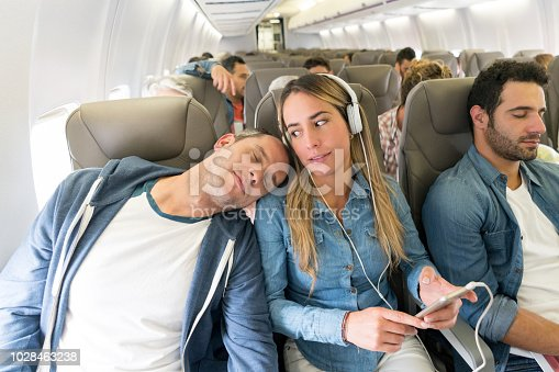 Rude man sleeping on a passenger's shoulder in an airplane while traveling by air - lifestyle concepts