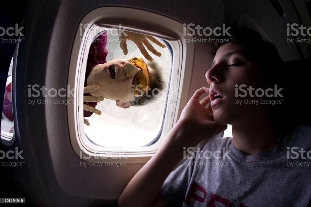 Man sleeping on an airplane with a skydiver stuck on window royalty-free stock photo