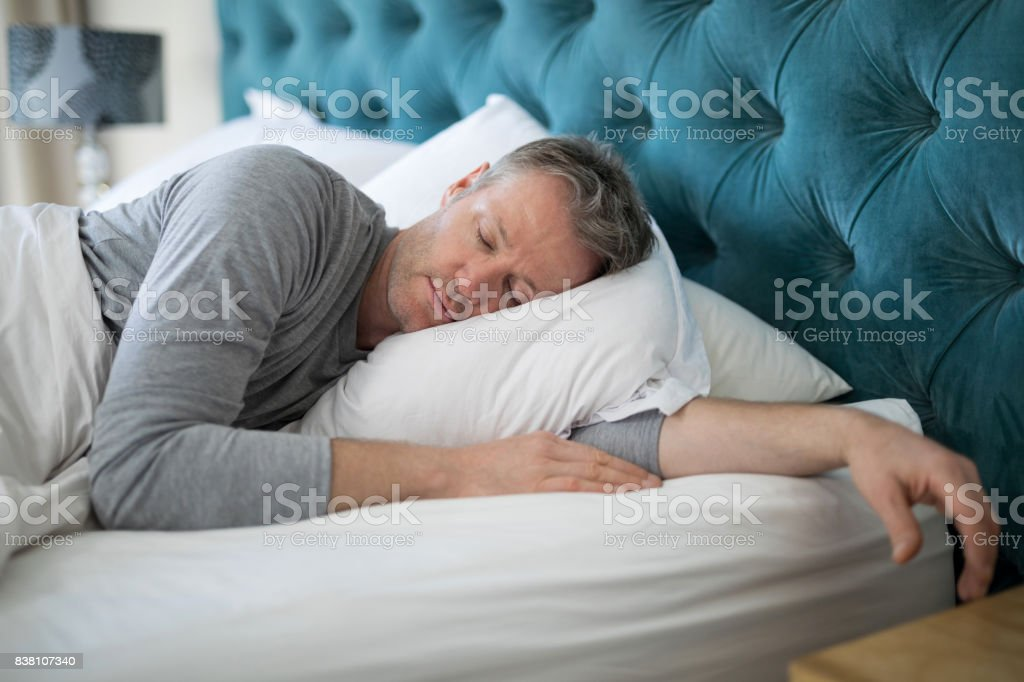 Man sleeping on bed in bedroom stock photo
