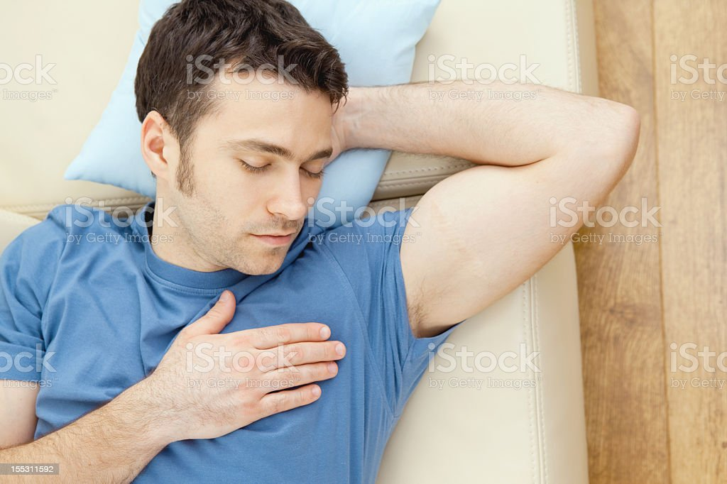 Young handsome man sleeping on couch at home, high-angle view. Click...