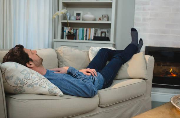 Man sleeping on sofa in living room stock photo