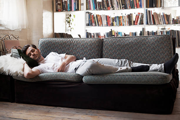 man sleeping on sofa - london themenzimmer stock-fotos und bilder